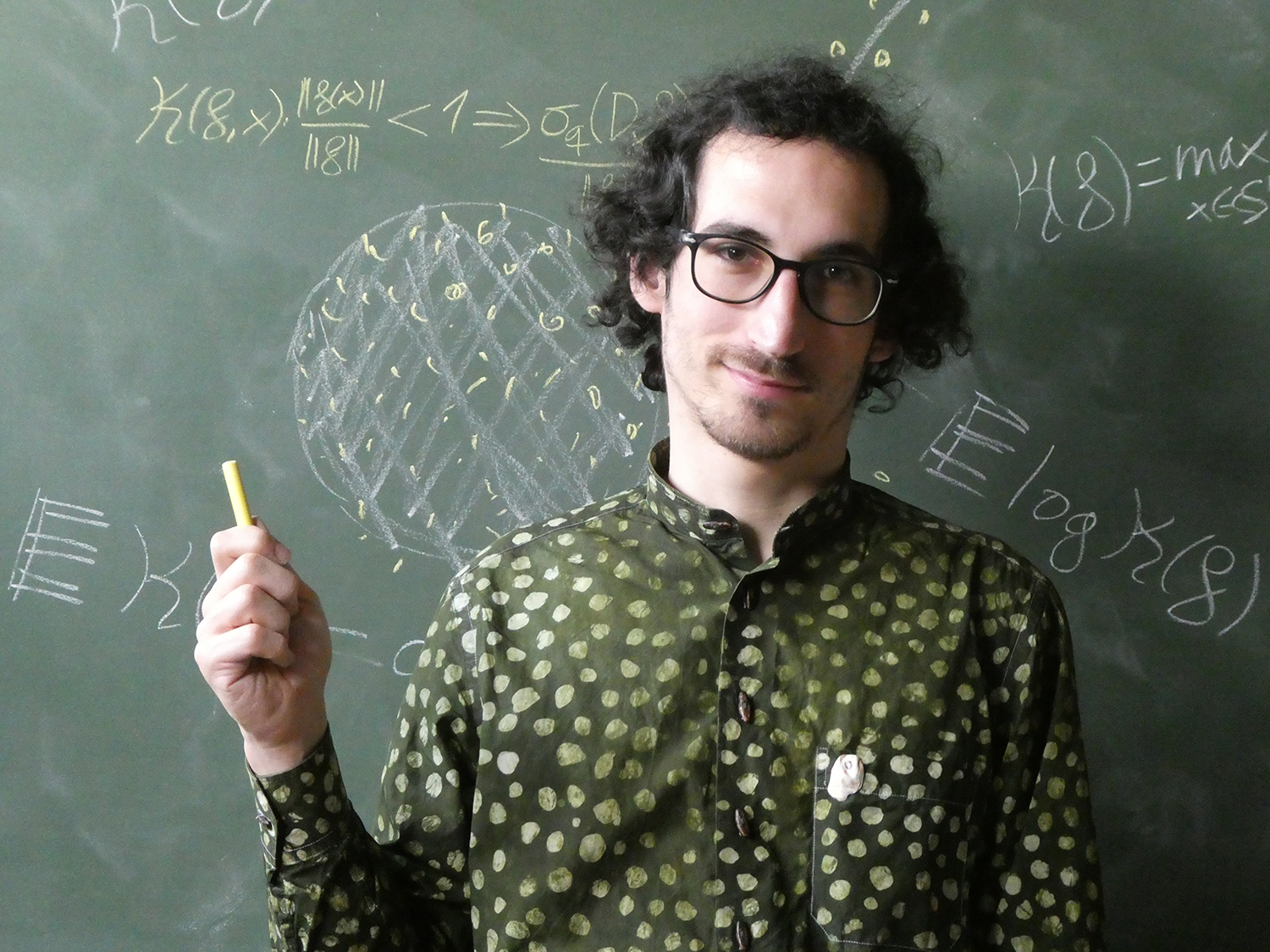 Josué Tonelli-Cueto in fron a blackboard holding a piece of chalk